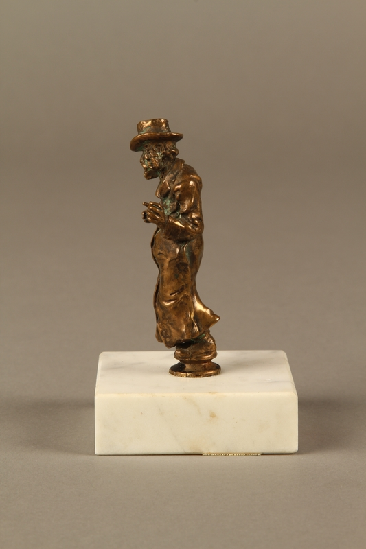 2016.184.147 left side Bronze figurine of a Jewish schnorrer in his traditional long coat