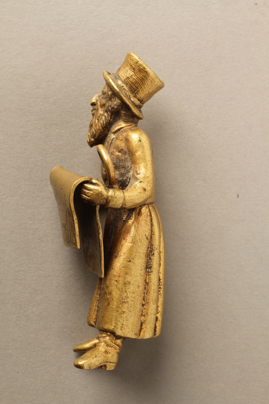 2016.184.148_a-b left side Bronze figurine of a Jewish man reading a newspaper