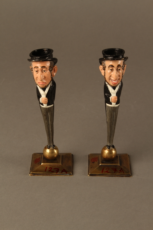 2016.184.154_a-b front Pair of painted candlesticks of a happy & a sad Jewish speculator
