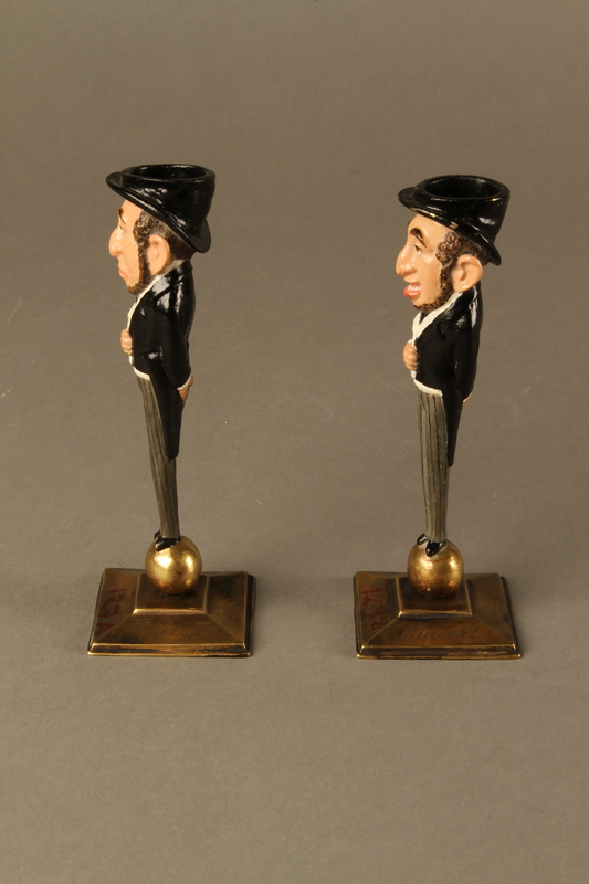 2016.184.154_a-b left Pair of painted candlesticks of a happy & a sad Jewish speculator