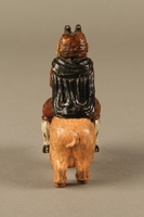 2016.184.206 back Painted metal figurine of a horned Jewish man with hooves riding a pig  Click to enlarge