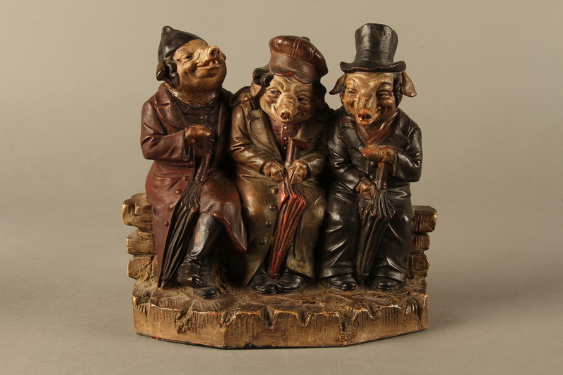 2016.184.211 front Ceramic figure group with 3 pigs as the stereotypical 3 Jews on a bench