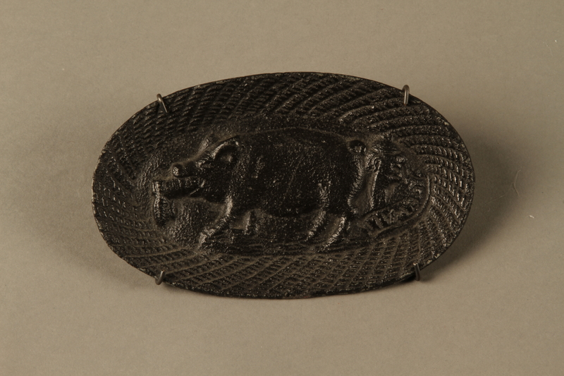 2016.184.210 front Iron dish with a Jewish man passing horizontally through a pig