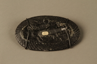 2016.184.210 back Iron dish with a Jewish man passing horizontally through a pig  Click to enlarge