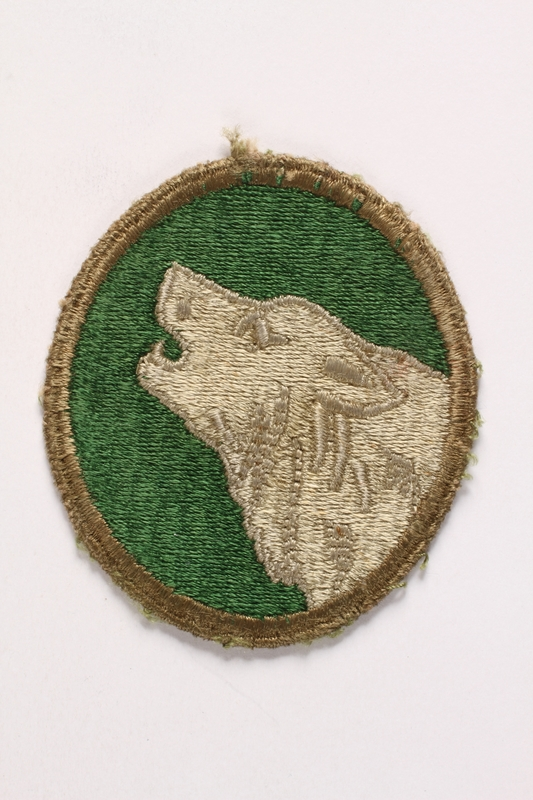 2003.149.87 front US Army 104th Infantry shoulder sleeve Timberwolf patch worn by a soldier