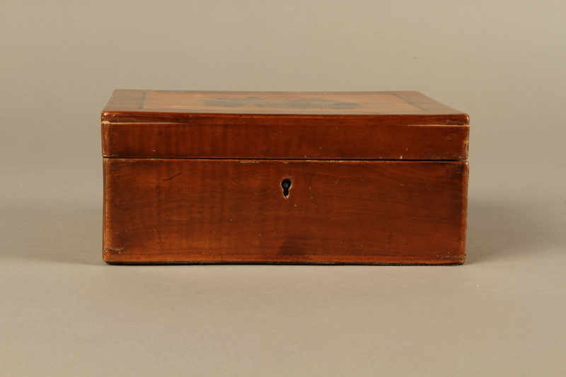 2016.184.532 front Wooden cigar box with an image of gossiping, stereotypical Jewish peddlers