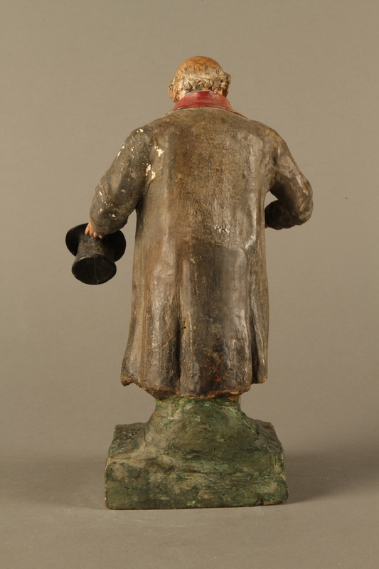2016.184.534.1 back Painted pottery figure of a stereotypical Jewish merchant holding gold coins
