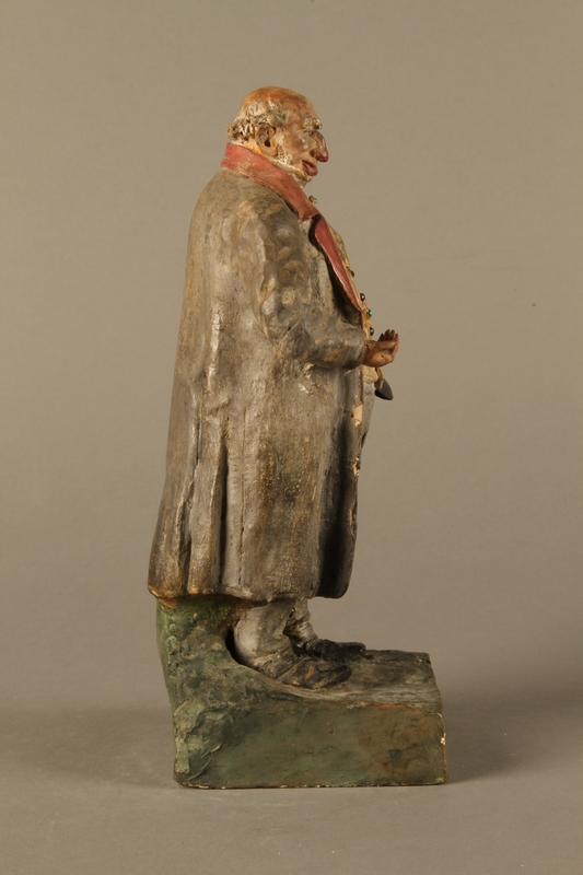 2016.184.534.1 right side Painted pottery figure of a stereotypical Jewish merchant holding gold coins