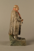 2016.184.534.1 right side Painted pottery figure of a stereotypical Jewish merchant holding gold coins  Click to enlarge