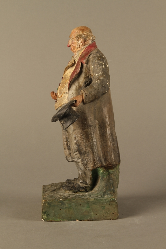 2016.184.534.1 left side Painted pottery figure of a stereotypical Jewish merchant holding gold coins