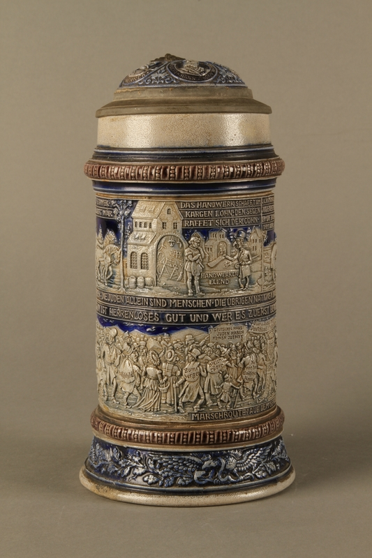2016.184.535 front Gray and blue beer stein with images of anti-Jewish fables and politicians