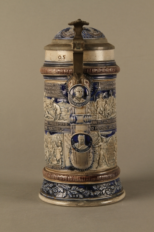2016.184.535 back Gray and blue beer stein with images of anti-Jewish fables and politicians