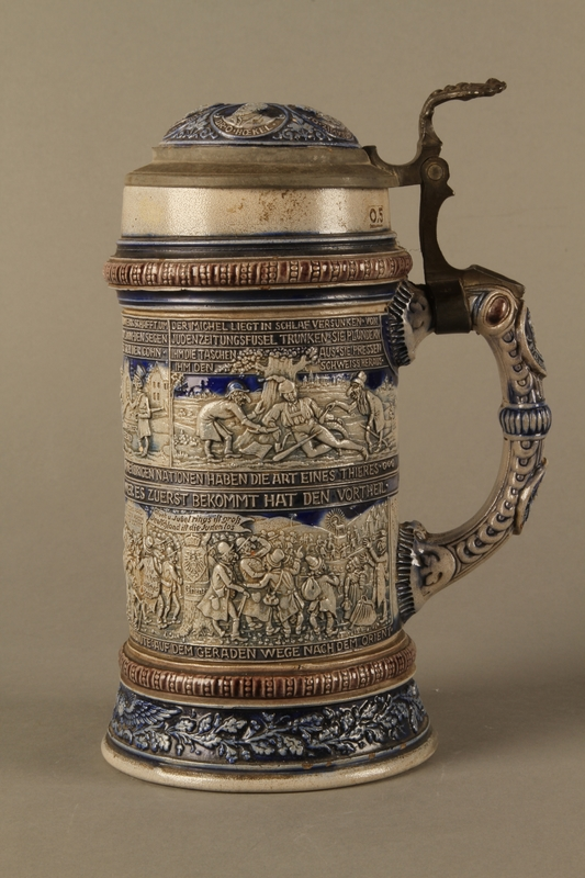 2016.184.535 left side Gray and blue beer stein with images of anti-Jewish fables and politicians