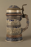 2016.184.535 left side Gray and blue beer stein with images of anti-Jewish fables and politicians  Click to enlarge