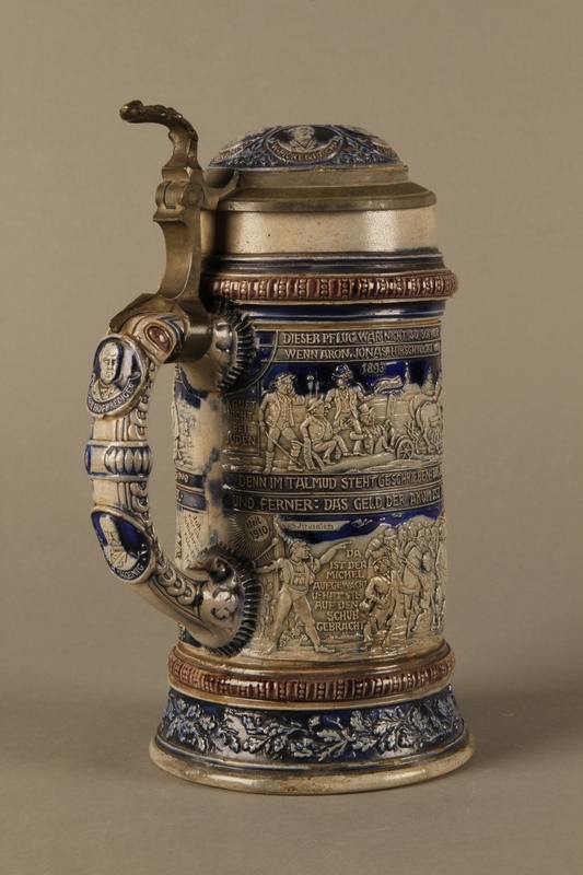 2016.184.535 closed 3/4 view Gray and blue beer stein with images of anti-Jewish fables and politicians