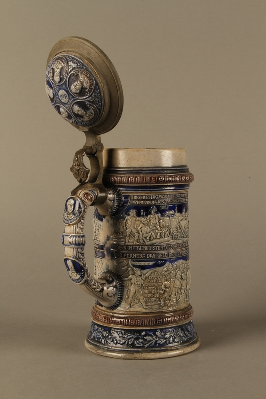 2016.184.535 open 3/4 view Gray and blue beer stein with images of anti-Jewish fables and politicians