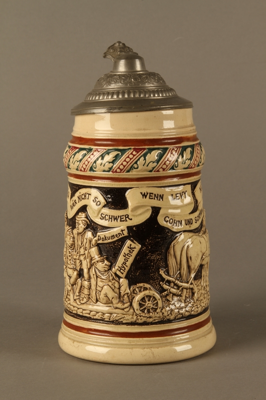 2016.184.536 front Black and cream ceramic beer stein with Jewish usurers tormenting a German farmer