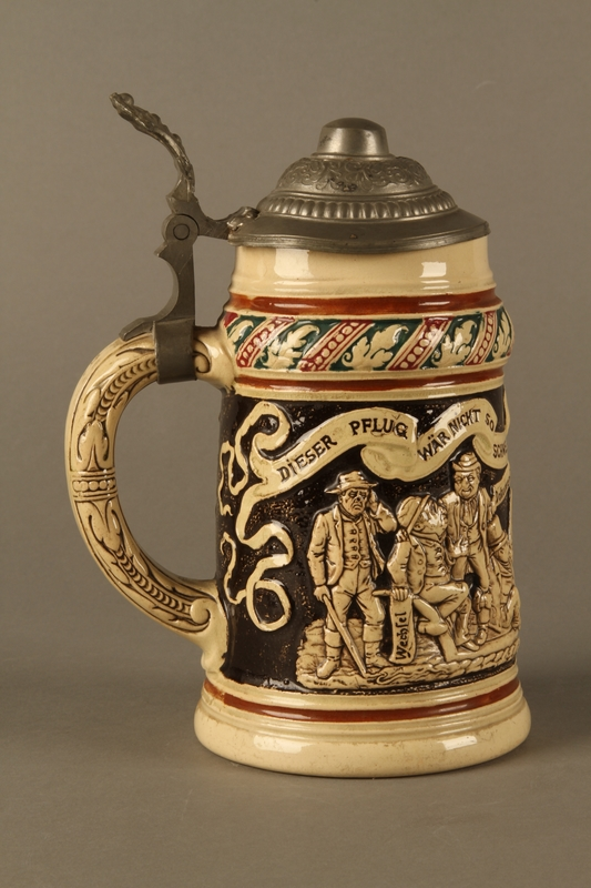 2016.184.536 right side Black and cream ceramic beer stein with Jewish usurers tormenting a German farmer