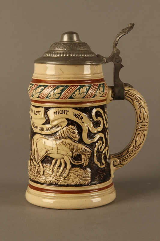 2016.184.536 left side Black and cream ceramic beer stein with Jewish usurers tormenting a German farmer