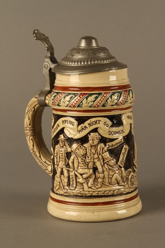 closed 3/4 view Black and cream ceramic beer stein with Jewish usurers tormenting a German farmer