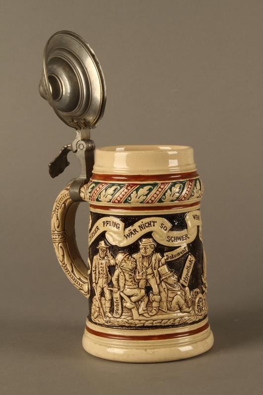 2016.184.536 open 3/4 view Black and cream ceramic beer stein with Jewish usurers tormenting a German farmer