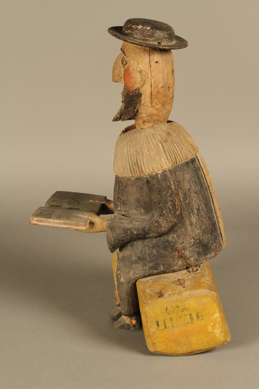 2016.184.566 a-b left Hand crafted wooden pull toy of a Jewish man praying