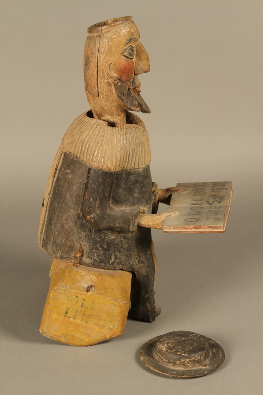 2016.184.566 a-b hat off Hand crafted wooden pull toy of a Jewish man praying