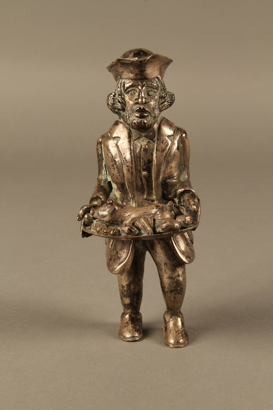 2016.184.569 front Metal figurine of a Jewish man carrying a tray with a suckling piglet