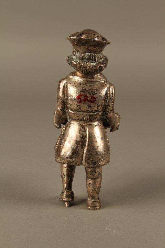 2016.184.569 back Metal figurine of a Jewish man carrying a tray with a suckling piglet