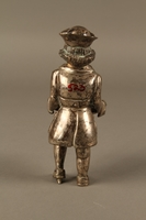 2016.184.569 back Metal figurine of a Jewish man carrying a tray with a suckling piglet  Click to enlarge