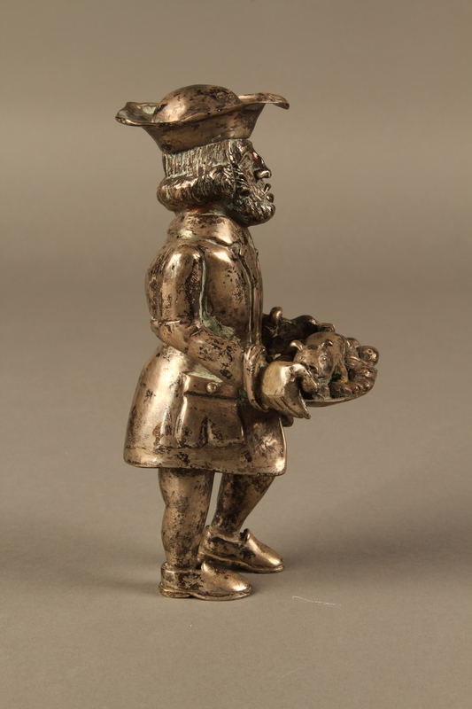 2016.184.569 right side Metal figurine of a Jewish man carrying a tray with a suckling piglet