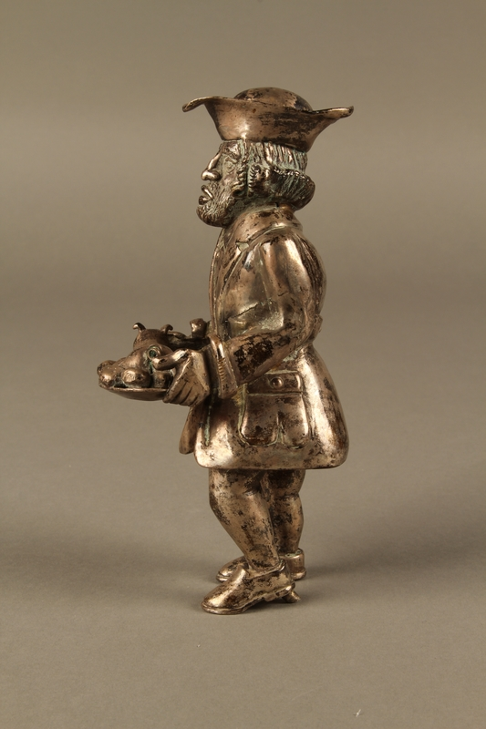 2016.184.569 left side Metal figurine of a Jewish man carrying a tray with a suckling piglet