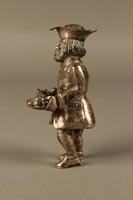 2016.184.569 left side Metal figurine of a Jewish man carrying a tray with a suckling piglet  Click to enlarge
