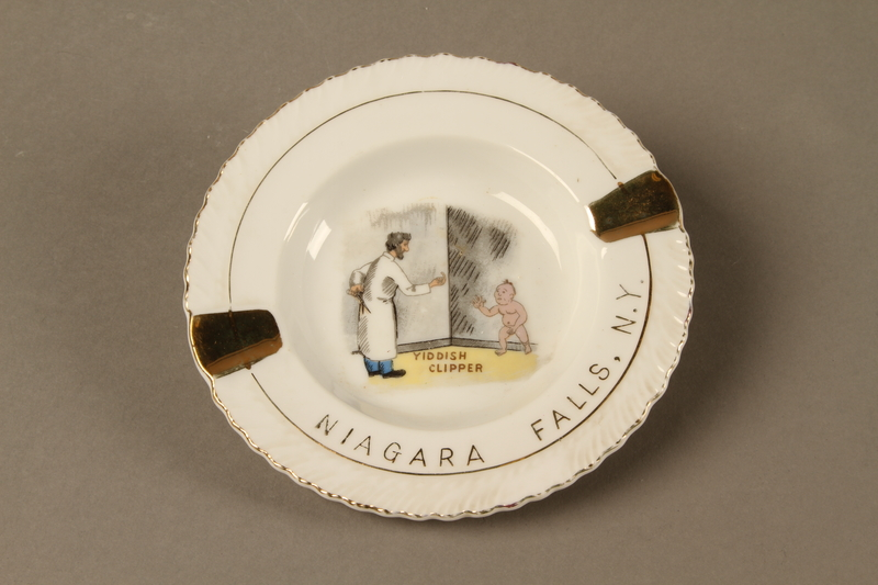 2016.184.574 front Souvenir ashtray of the Yiddish clipper, a man with scissors and a naked boy