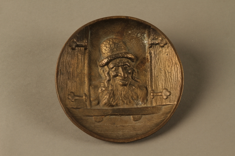 2016.184.587 front Bronze metal dish of a Jewish peddler at an open window