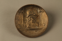 2016.184.587 front Bronze metal dish of a Jewish peddler at an open window  Click to enlarge