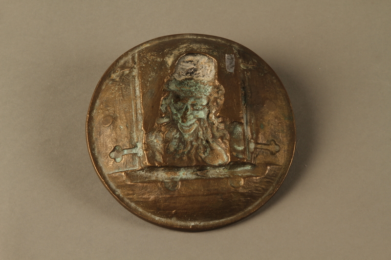2016.184.587 back Bronze metal dish of a Jewish peddler at an open window