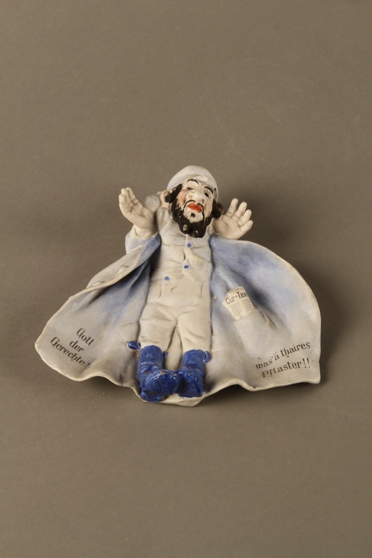 2016.184.588 front Bisque dish of a Jewish man in a white plasterer's coat with blue boots