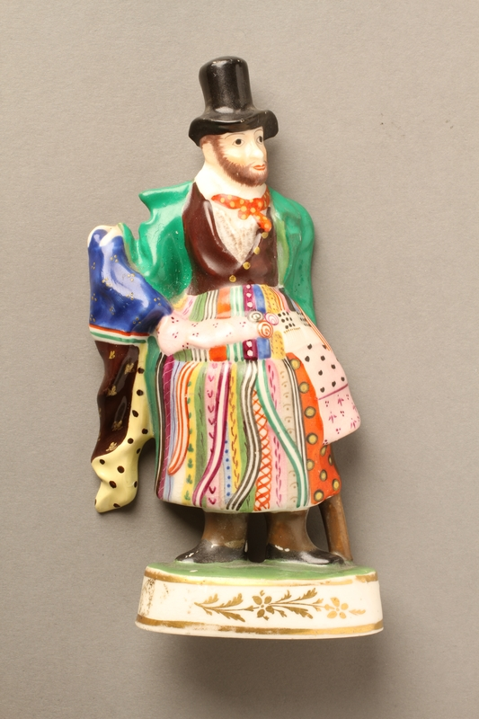 2016.184.593 front Porcelain figurine of a Jewish ribbon peddler in a green coat