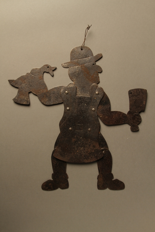2016.184.596 front Hand cut, movable metal figure of a ritual butcher
