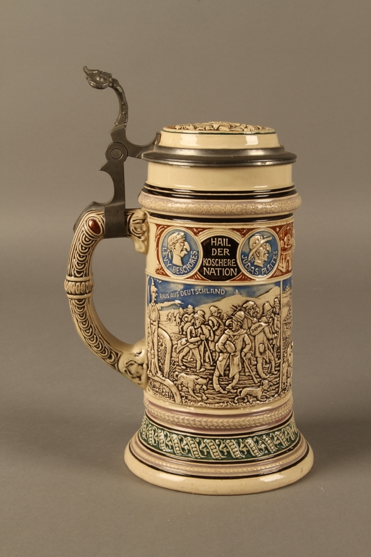 2016.184.603 front Blue, green, and brown beer stein with images of the expulsion of the Jews
