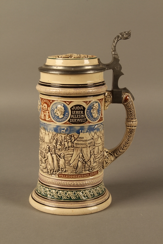 2016.184.603 back Blue, green, and brown beer stein with images of the expulsion of the Jews