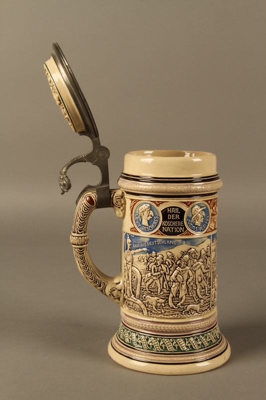 2016.184.603 open Blue, green, and brown beer stein with images of the expulsion of the Jews