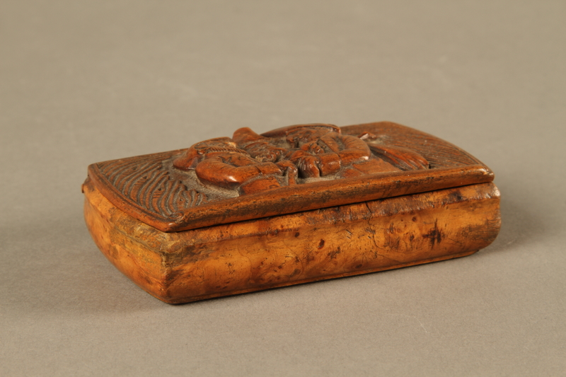2016.184.606 closed Carved snuff box with a carving of three Jewish hareskin dealers