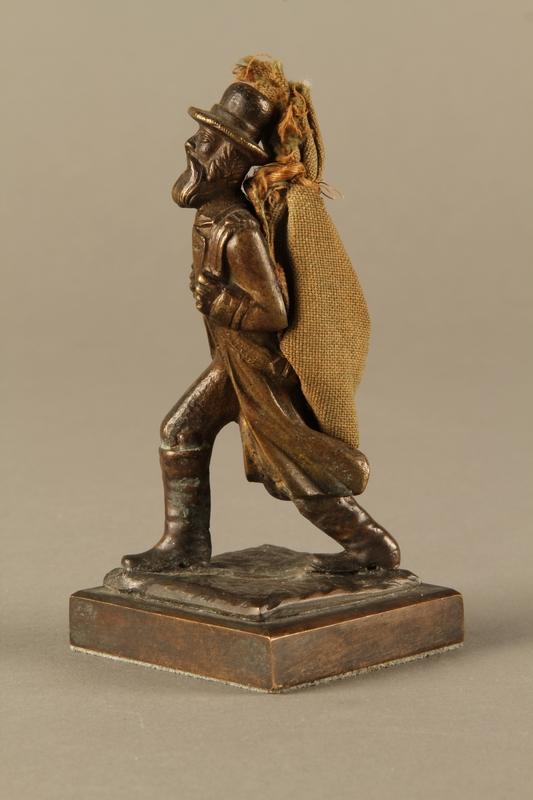 2016.184.611 left side Bronze figurine of a Jewish peddler with a burlap sack