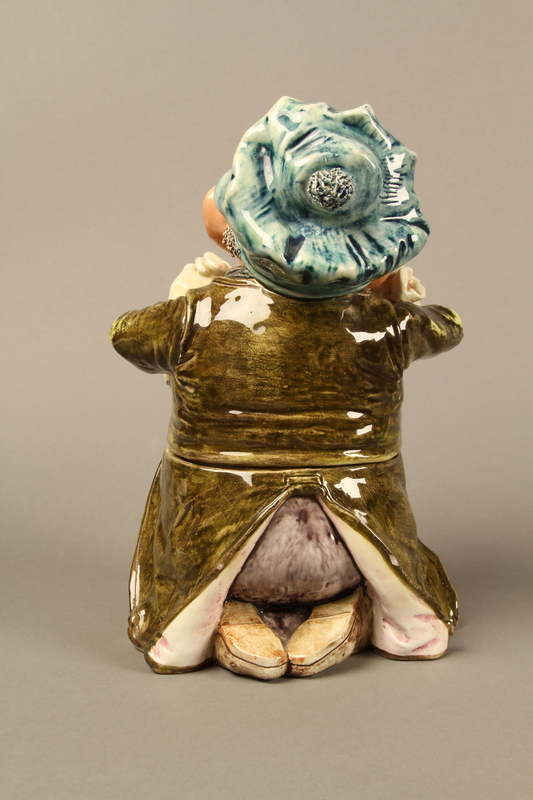 2016.184.620_a-b back Ceramic cookie jar of a Jewish man kneeling with 2 money bags