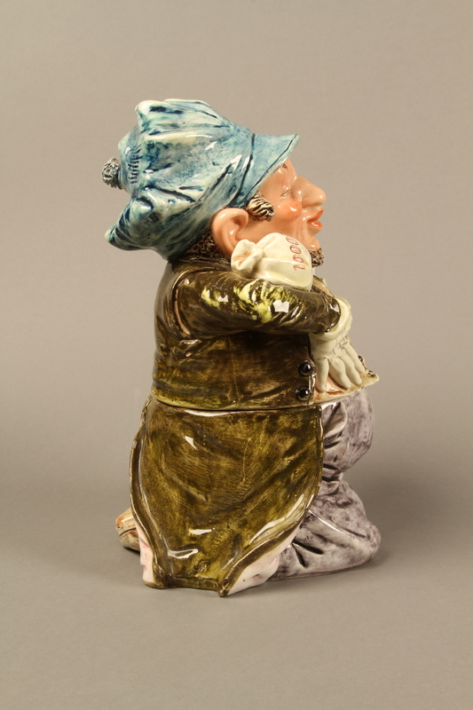 2016.184.620_a-b right Ceramic cookie jar of a Jewish man kneeling with 2 money bags