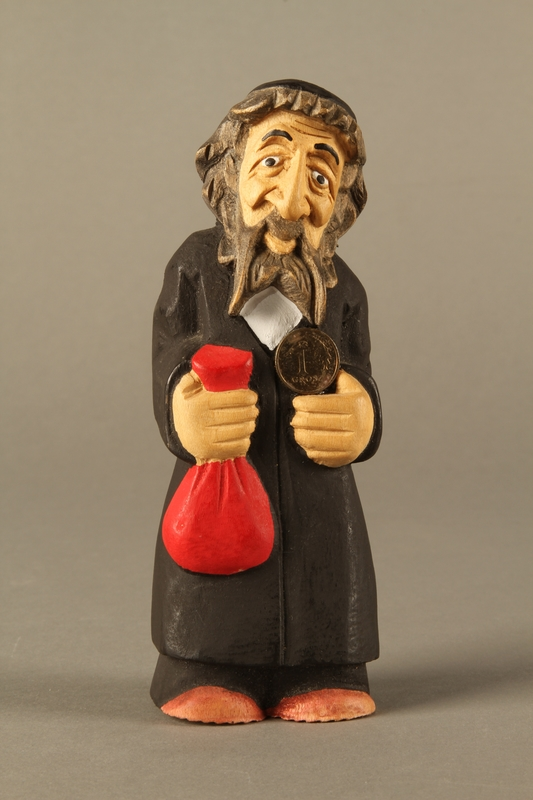 2016.184.622 front Wooden figurine of a Jewish man with a Judenstern and red bag