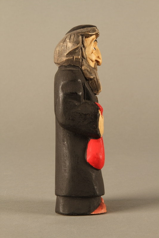 2016.184.622 right side Wooden figurine of a Jewish man with a Judenstern and red bag