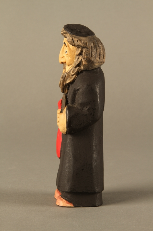 2016.184.622 left side Wooden figurine of a Jewish man with a Judenstern and red bag